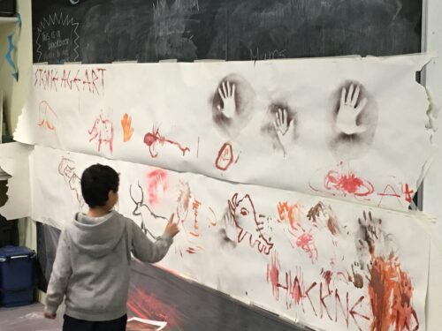 Photograph of child stood in front of artwork created at community event.