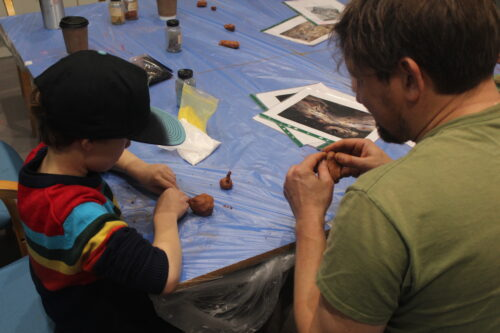Picture showing a child and an adult making animal figures out of clay